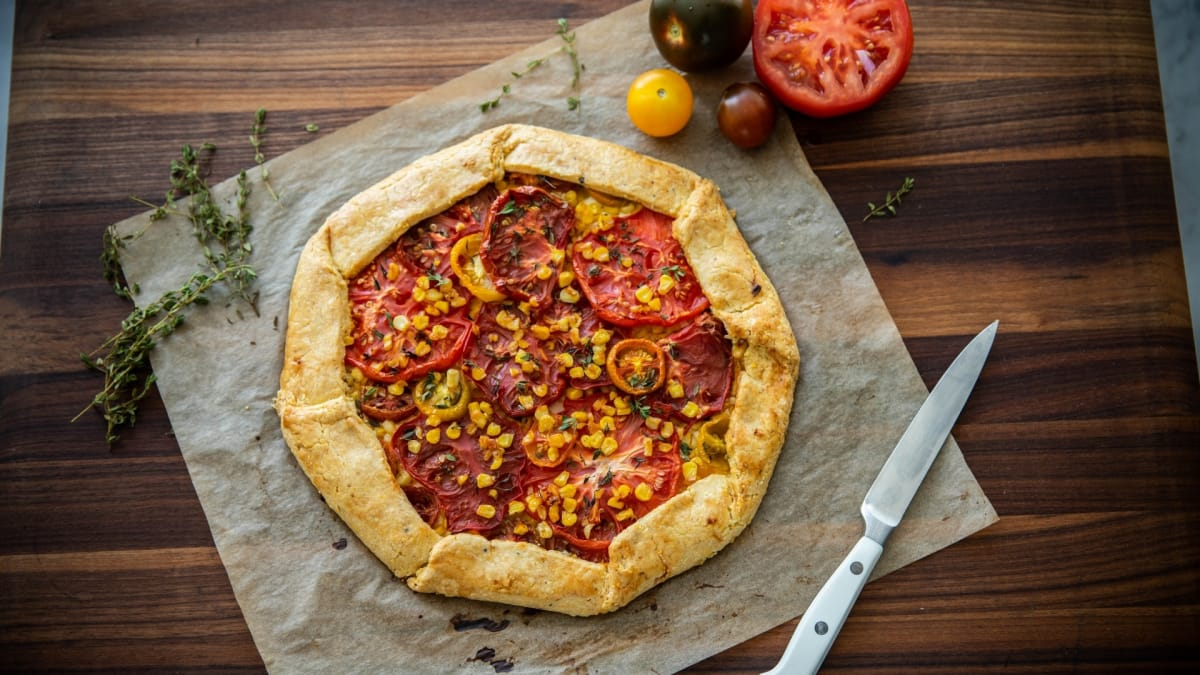 This cornmeal galette is topped with sweet corn and a variety of tomatoes.